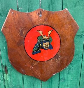 wooden shield on green wooden wall. Shield has red circle on r with green and blue samurai helmet
