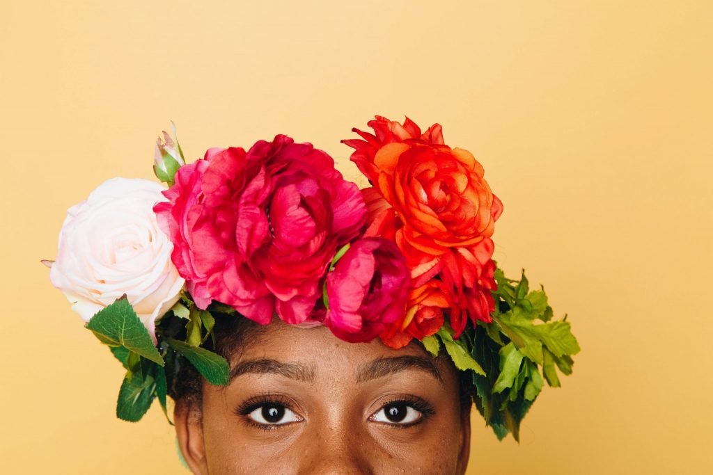 eyes and top of lady's head, with flowers on her head , white, red and orange