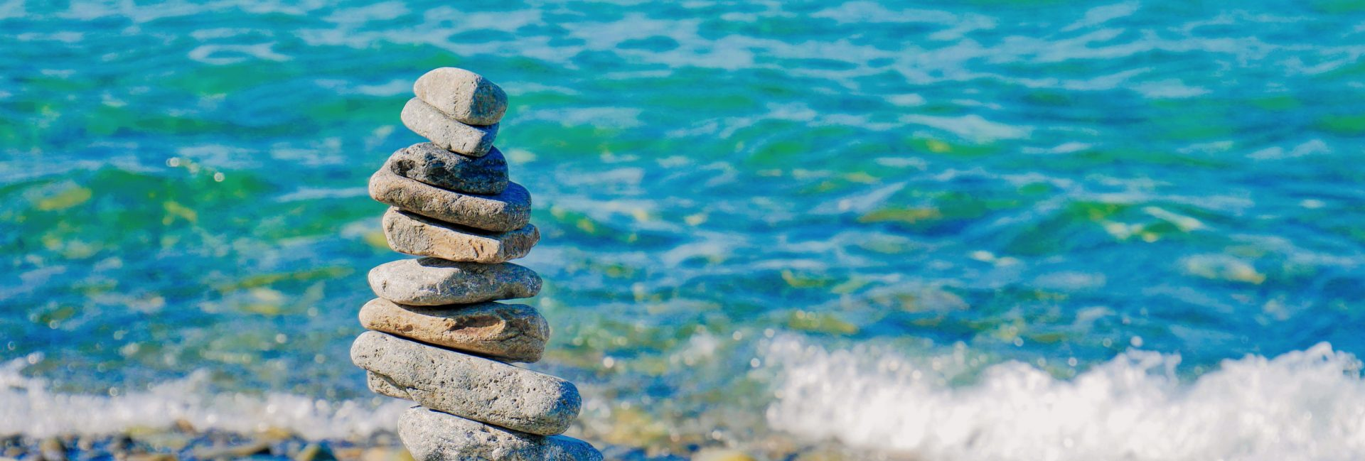 Stones balanced in a tower next to a beautiful blue sea