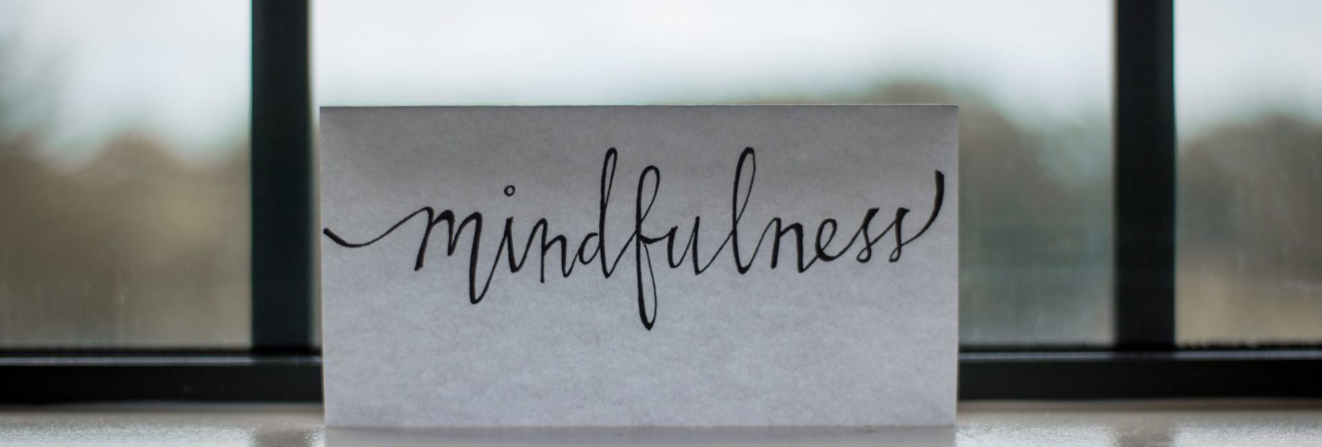 note in front of a window, with nice hand writing saying mindfulness