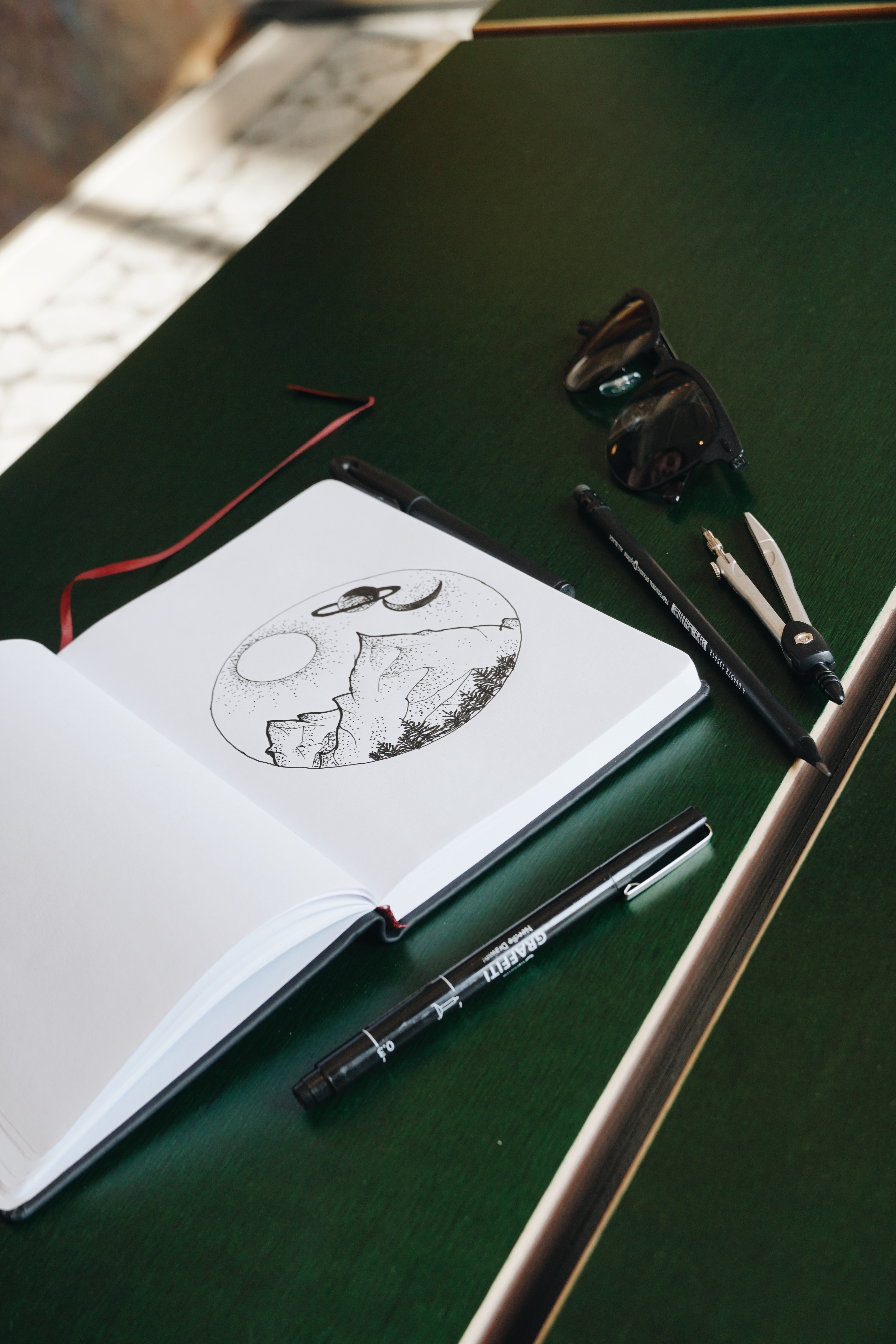 journal with drawings of mountains in a circle, equipment around it on desk