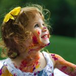 little girl covered in colourful paint with yellow ribbon in hair