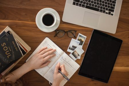 woman's hands wring in journal, at peak with glasses, coffee, photos , lauotio, books