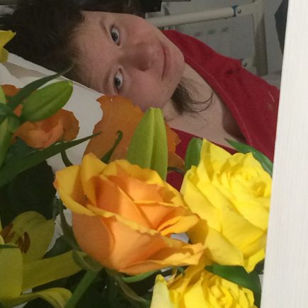 Jade in hospital bed with roses