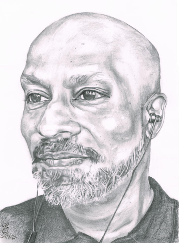 Portrait of bald man with beard looking off to his right, wearing ear buds