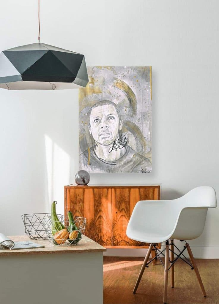 Photo of a room with a brown side table against a white wall. Above the side table is a drawing of the singer Will Young.